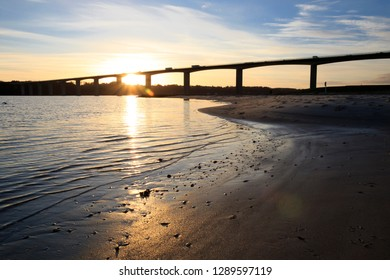 Bridge and beach in sunset with reflexions in water.