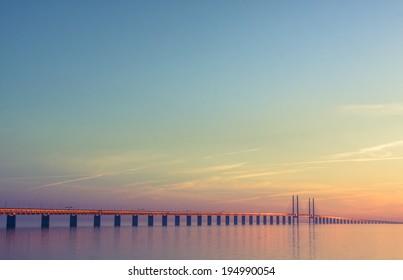 The bridge between Denmark and Sweden, Oresundsbron, in summer sunset with calm weather.