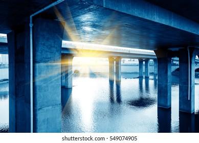 Bridge at the bottom of piers, modern building blue tones.