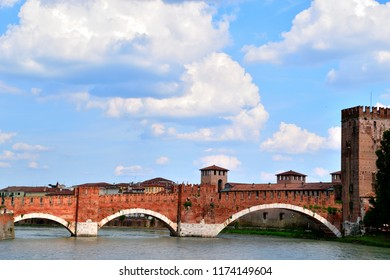 The bridge of Castelvecchio, in Verona, permits to pass the Adige river and to reach the castle. The sky is blue but cloudy.
