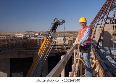 bridge construction worker by heavy construction equipment