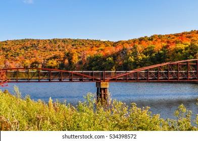 A bridge crosses a small lake near in front of the autumn colors near Rutland, Vermont.