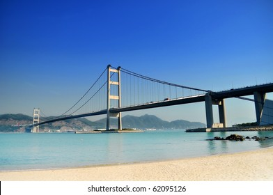 Bridge crossing the sea to an island under a clear blue sky just next to a white sand beach.