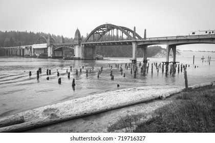 Bridge crossings and river with tree stumps, Florence OR, USA. Siuslaw River Bridge from the Florence Marina Oregon USA