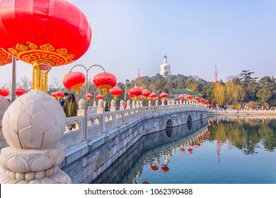 The bridge, decorated with traditional red lanterns in honor of the Chinese New Year leading to the Jade Island with White Pagoda in Beihai Park, Beijing, China