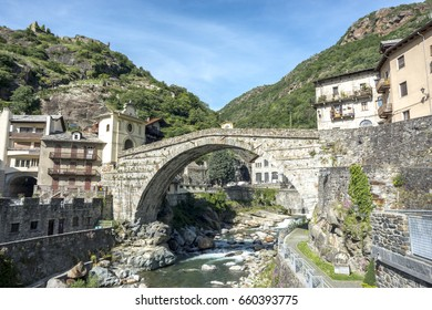 """The bridge of the devil at Pont Saint Martin, Located on the border with Piedmont and is the """"gateway to Valle d'Aosta"""", Italy. The bridge is located in a valley of the Alps. Blue sky, green mountains"""