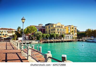 Bridge embankment yacht pier Lake Garda restaurants hotels luxury resort Sirmione Italy.