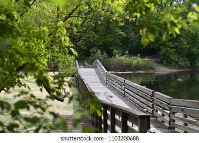 Bridge extending over lake during first days of summer. Pedestrian bridge at lake park in Eagan, Minnesota.
