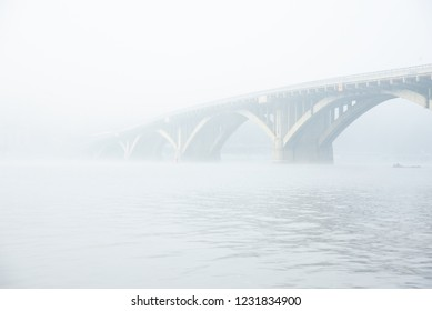 Bridge in the fog over the river. The bridge in the autumn at a morning fog.