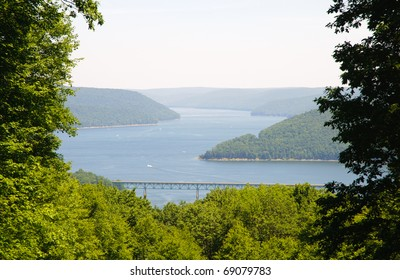 bridge framed by trees from an overlook of the Allegheny National Forest and reservoir