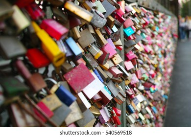 a bridge full of colorful love locks with some names written on it. Most of them look old and vintage.