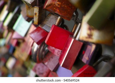 a bridge full of colorful love locks with some names written on it. Most of them look old.