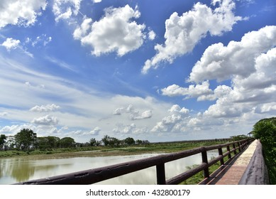 Bridge with green trees, blue sky background.