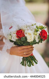 A bridge and groom holds a bouquet of red rose flowers together.