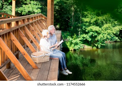 Bridge and hamper. Elderly wife and husband sitting on the wooden bridge near hamper while having traditional picnic