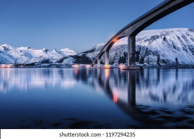Bridge with illumination, snow covered mountains, village and blue sky with reflection in water. Night landscape with bridge, snowy rocks reflected in sea. Winter in Lofoten islands, Norway. Roadway