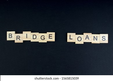 Bridge loans- word composed fromwooden blocks letters on black background, copy space for ad text