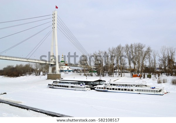 The bridge of lovers through the Tura River and the embankment in Tyumen in the winter. Russia, on February 17, 2017