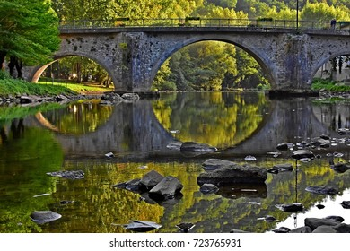 Bridge mirrored in rock strewn river