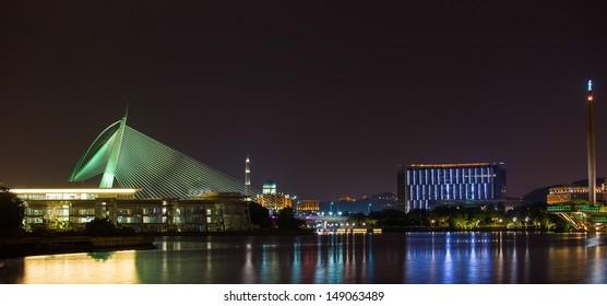 A bridge and modern buildings in Putrajaya, Malaysia at night