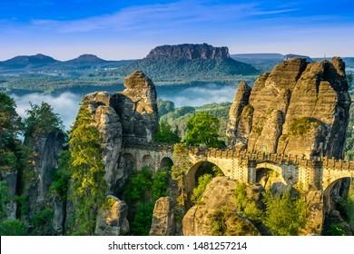 Bridge named Bastei in Saxon Switzerland,  at sunrise and the mist over the river Elbe, National park Saxon Switzerland