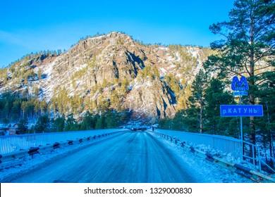 "The bridge near Askat village over frozen Katun river in Altai Mountains. Russian winter in Siberia. Translation is ""Katun river""."