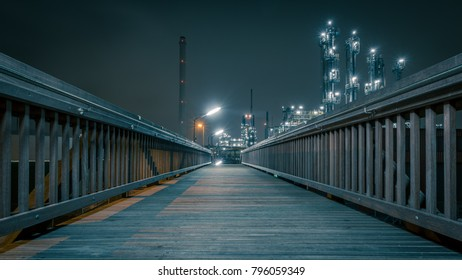 bridge at night leading to a wel lit industrial plant of an oil refinery