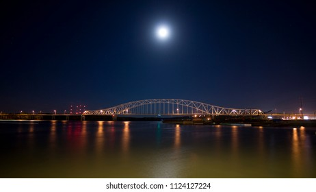 Bridge at night over the mighty Mississippi river barges