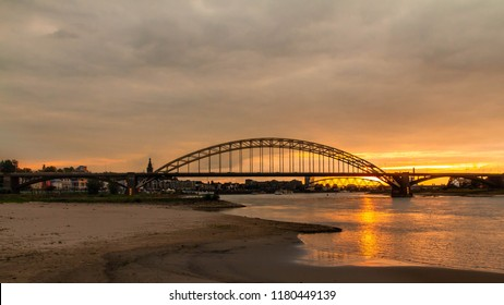 Bridge of Nijmegen during sunset with typical dutch cloudy sky, Netherlands