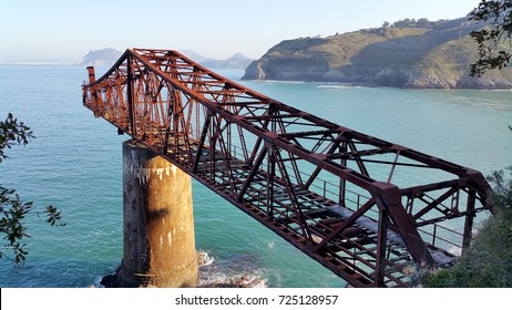 Bridge to nowhere. Abandoned overpass for loading ore from an old mine on the seashore. View from above, against the background of the sea. Miono, Cantabria, North spain.