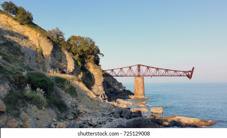 Bridge to nowhere. Abandoned overpass for loading ore from an old mine on the seashore. Against the background of the sea. Miono, Cantabria, North spain.