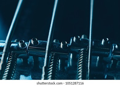 Bridge on bass guitar. Close up. Vintage old retro bass in studio. Trendy cold style