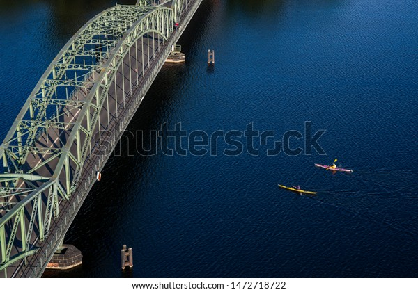 Bridge on a large body of water on which tourists practice water sports.