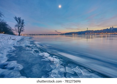 Bridge on the River Dnieper in the evening. Lantern light is reflected in the frozen ice, city, Ukraine