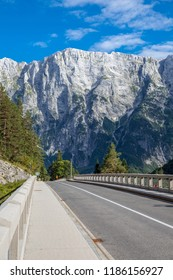 Bridge on a summit road between Slovenia and Italy. Street in the Julian Alps. Mountain road in front of a impressive rockface. Mountains in the background.