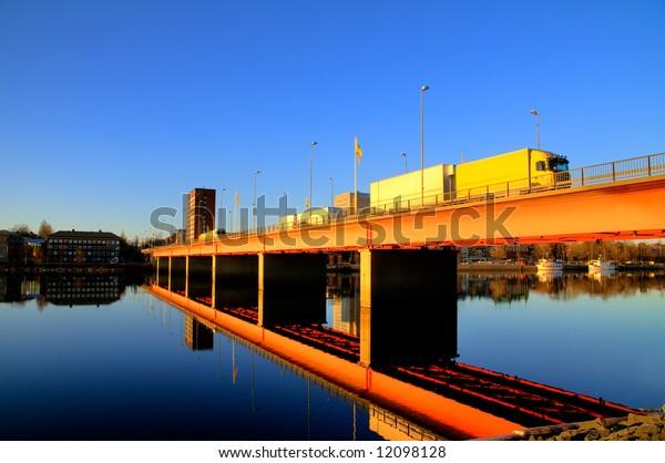 bridge over a calm river at sundown