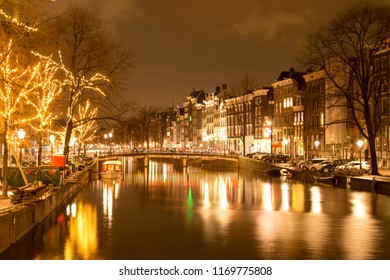 Bridge over a canal in Amsterdam at night with lights reflecting in the water