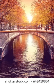 Bridge over channel in Amsterdam Netherlands autumn urban landscape with yellow tree on bank river sunny day old european town.