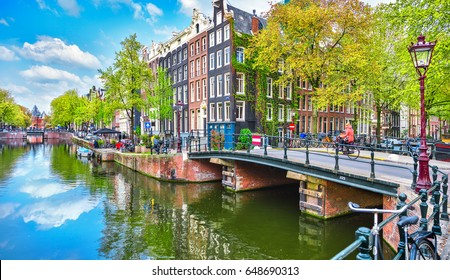 Bridge over channel in Amsterdam Netherlands houses river Amstel landmark old european city spring landscape.