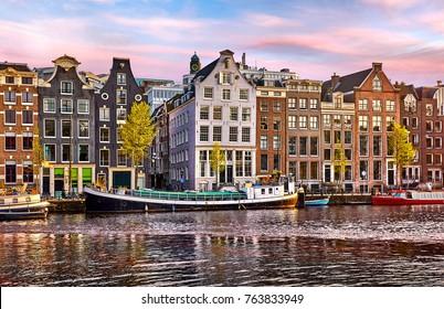 Bridge over channel in Amsterdam Netherlands houses river Amstel landmark old european city spring landscape