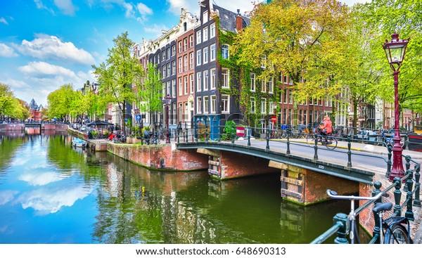 Die Brücke über den Kanal in Amsterdam Niederlande beherbergt den Fluss Amstel Wahrzeichen der alten europäischen Stadt Frühjahrslandschaft.