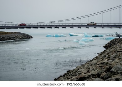 Bridge over Jokulsarlon glacier lagoon in Iceland with floating blue Icebergs, water, and passing cars