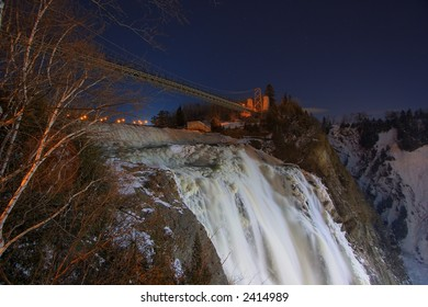 A bridge over Montmorency Falls shot at night
