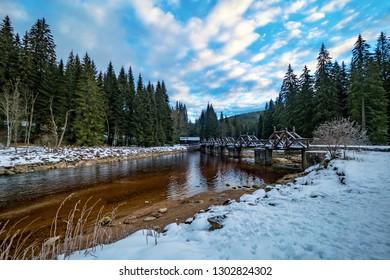 Bridge over a mountain river in a snowy landscape