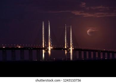 The bridge over Oresund between Malmo Sweden and Copenhagen Denmark when evening and moon