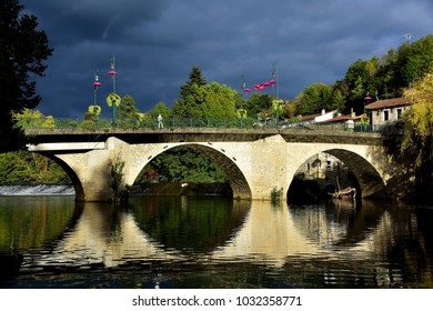 The bridge over the river Agout at Roquecourbe, Southern France. In spite of the dark stormy sky the bridge is sunlit giving a beautiful reflection in the river.