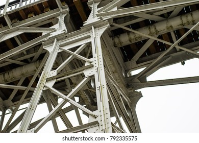 A bridge over a river built from a truss. Bridge, truss joined by rivets in old technology on the river. Winter campery.