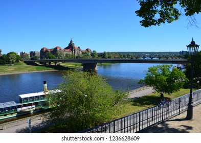 Bridge over river Elbe in the city of Dresden in Germany, biking trails on both sides of the river bank, excursion boats on the docks