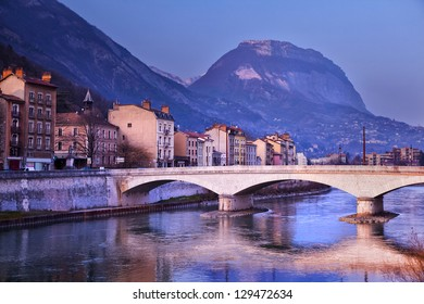 A bridge over River Isere in Grenoble, France. A part of the Alpes in the background