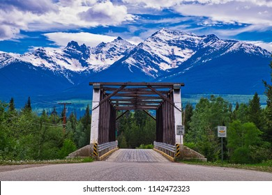 Bridge over a river to the mountains. A beautiful scenery in the Rocky Mountains. Clouds and snow on the mountains makes a perfect canvas.
